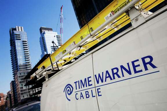 In this file photo, a Time Warner Cable truck is parked in New York.  Cable TV operator Charter Communications said Monday, Jan. 13, 2014, it wants to buy the much larger Time Warner Cable in a cash-and-stock deal that could be worth up to $38 billion. (AP Photo/Mark Lennihan, file)
