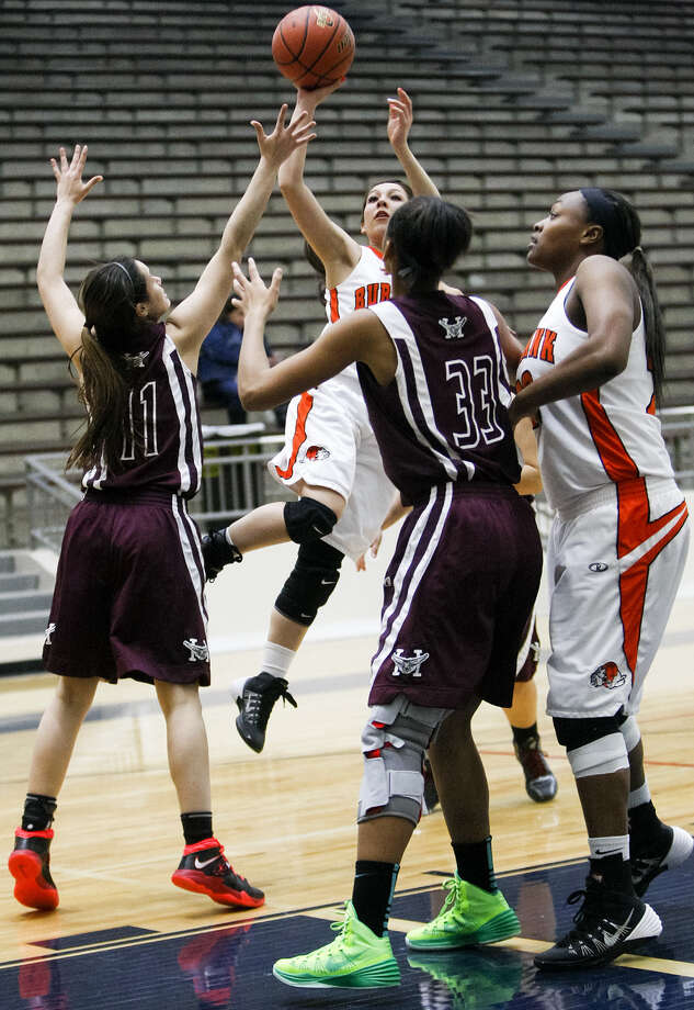 Burbank's Alejandra Martinez, top center, shoots over Highlands' Emily Pearce, from left, and Jazmine Jackson as Antwanisha Riddle looks on during a game at the Alamo Convocation Center on Jan. 7. Photo: Marvin Pfeiffer / Southside Reporter / Express-News 2014