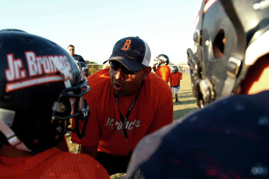 FRIDAY NIGHT TYKES -- Season: 1 -- Jr. Broncos Coach Charles Charles Chavarria talks to players on camera during the taping of the reality television show Friday Night Tykes. Chavarria and another coach were suspended for their actions on the show. Chavarria was suspended for one year. The other coach Marecus Goodloe was suspended for six games.   -- (Photo by: Walter Iooss/Esquire Network)