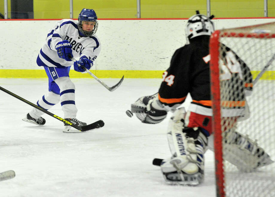 Darien's Georgia Cassidy shoots on Stamford/Westhill/Staples goalie Casey Bang during their hockey game at Terry Conners Rink in Stamford, Conn., on Monday, Jan. 13, 2014. Darien won, 7-0. Photo: Jason Rearick / Stamford Advocate