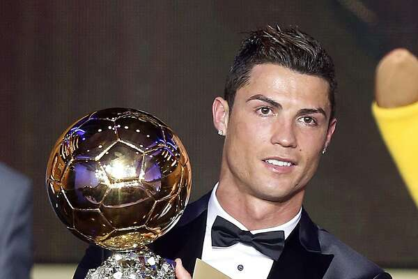 Real Madrid's Christiano Ronaldo of Portugal holds the trophy for world player of the year at the FIFA Ballon d'Or 2013 Gala in Zurich, Switzerland, Monday, Jan. 13, 2014. (AP Photo/Michael Probst)