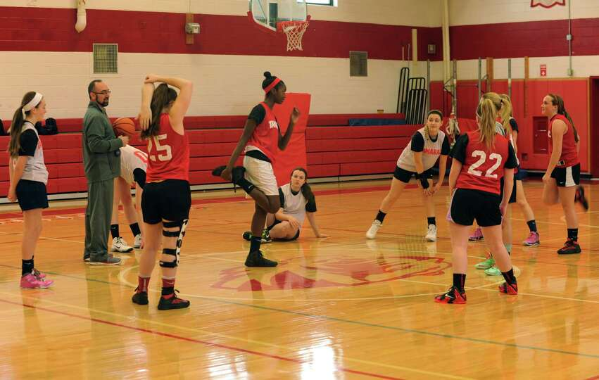 Tamarac senior center Adiya Henderson, center, is surrounded by her teammates as she leads a stretch