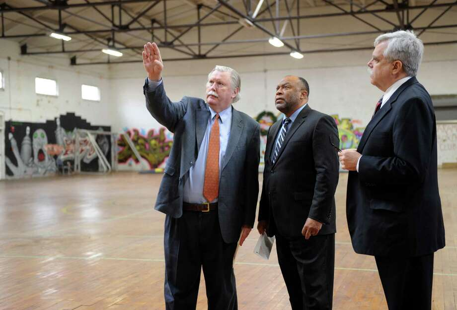 From left, James Maloney, president and CEO of Connecticut Institute for Communities, Rodrick Bremby, commissioner of the Connecticut Department of Social Services and state Rep. Robert Godfrey, tour the old Danbury Armory, Monday, January 13, 2014. Photo: Carol Kaliff / The News-Times