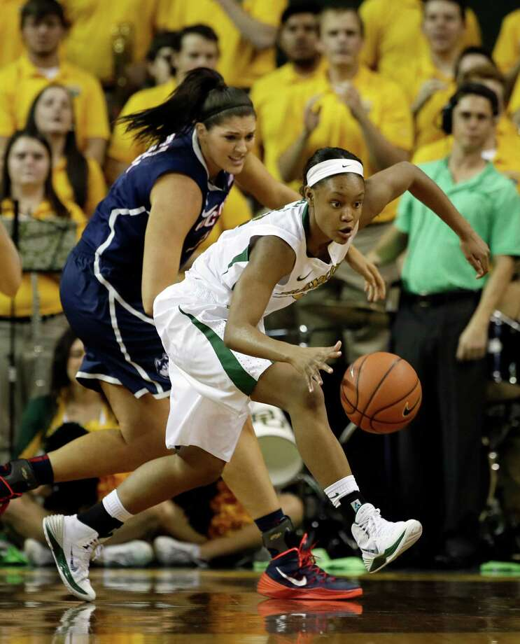 Baylor's Nina Davis (13) handles the ball around the perimeter as Connecticut center Stefanie Dolson, rear, defends in the first half of an NCAA college basketball game, Monday, Jan. 13, 2014, in Waco, Texas. Connecticut won 66-55. Photo: Tony Gutierrez, AP / Associated Press