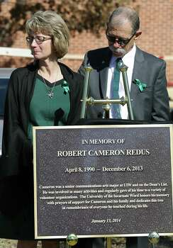Mickey, right, and Valerie Redus, parents of Robert Cameron Redus, stand by a marker that is next to a tree planted in memory of the University of the Incarnate Word student that was fatally shot by a UIW officer. Monday, Jan. 13, 2013. Photo: BOB OWEN, San Antonio Express-News / © 2012 San Antonio Express-News