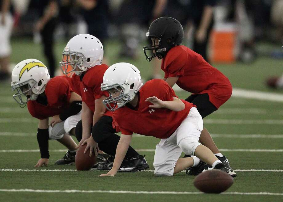 Young kids line up as they practice a drill during the Houston Texans' Youth Football Camp at Methodist Training Center, Tuesday, July 17, 2012, in Houston. The camp is for both both flag and tackle and open to children 8-14.  Karen Warren / Houston Chronicle ) Photo: Karen Warren, Staff / © 2012  Houston Chronicle