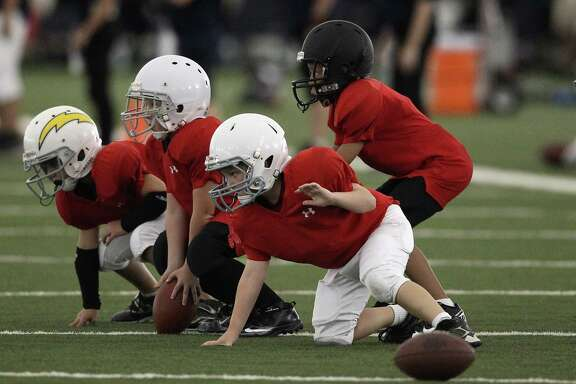 Young kids line up as they practice a drill during the Houston Texans' Youth Football Camp at Methodist Training Center, Tuesday, July 17, 2012, in Houston. The camp is for both both flag and tackle and open to children 8-14.  Karen Warren / Houston Chronicle )