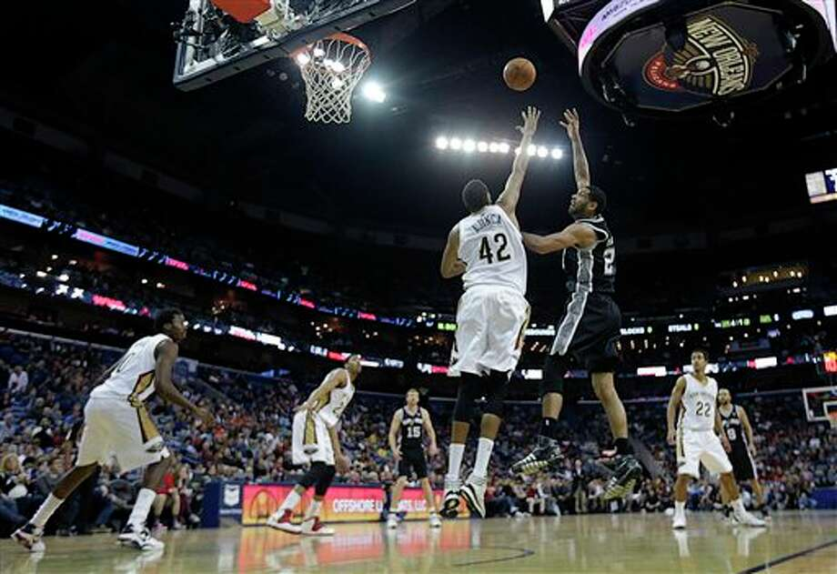 San Antonio Spurs power forward Tim Duncan shoots over New Orleans Pelicans center Alexis Ajinca (42) in the first half of an NBA basketball game in New Orleans, Monday, Jan. 13, 2014. (AP Photo/Gerald Herbert) Photo: Gerald Herbert, AP / AP