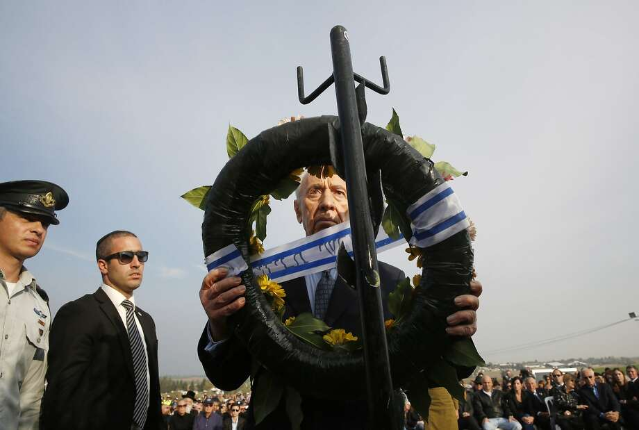 HAVAT HASHIKMIM, ISRAEL - JANUARY 13:  Israel's President Shimon Peres lays a wreath during the funeral of former Israeli Prime Minister Ariel Sharon near Sycamore Farm on January 13, 2014 in Havat Hashikmim, Israel. Former PM Ariel Sharon's died on Saturday aged 85 in Tel Hashomer hospital near Tel Aviv and had been in a coma since January 4, 2006.  (Photo by Baz Ratner - Pool/Getty Images) *** BESTPIX *** Photo: Pool, Getty Images