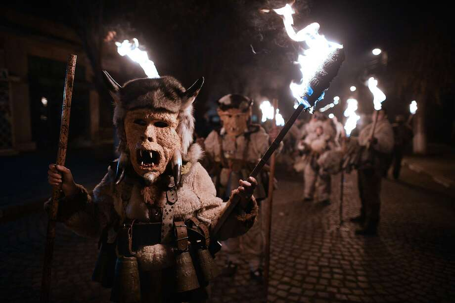 Banishing evil: Torch-bearing masked figures known as Kukeri march through the village of Batanovci, Bulgaria, in a traditional ritual to drive away evil spirits and promote a successful growing season. The costumes include bells tied around the waist to drive away demons and sickness. Photo: Dimitar Dilkoff, AFP/Getty Images