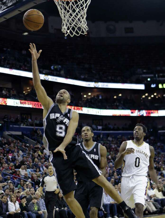 Spurs point guard Tony Parker jets to the basket for a layup en route to scoring 27 points as teammate Kawhi Leonard and Pelicans forward Al-Farouq Aminu trail the play. Parker also had seven assists. Photo: Gerald Herbert / Associated Press / AP