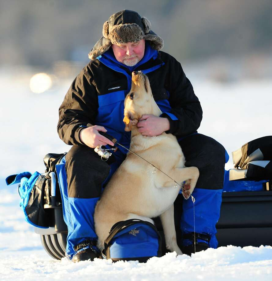 Max would rather play with Jeff Wohl than wait patiently for a walleye to bite at Government Point on Minnesota's frozen Gull Lake. Photo: Steve Kohls, Associated Press