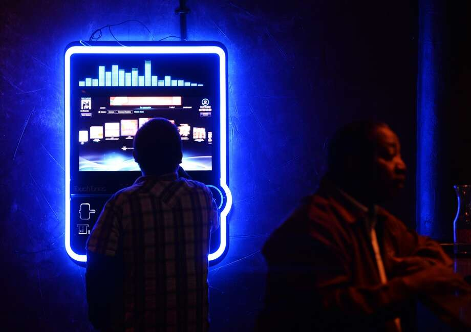Miguel Villasana looks over an electronic jukebox at the Pacesetter Lounge on Monday night. Pacesetter Lounge on Phelan Boulevard is the CAT5 Bar of the Week for January 9, 2014. The lounge shut down last October but reopened just a few weeks later. Photo taken Monday, 12/30/13 Jake Daniels/@JakeD_in_SETX