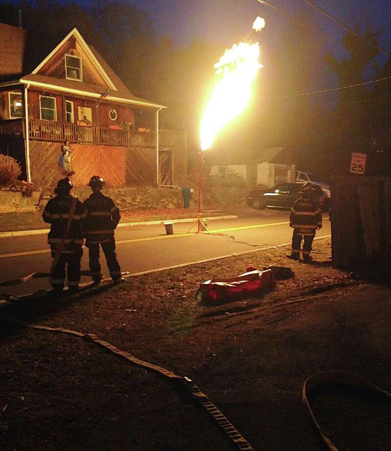 Firefighters use a flare tower to burn off gas leaking from a deteriorating propane tank Monday. The tank was discovered in a Longfellow Avenue yard, and the hazmat burn-off was staged nearby in the middle of Castle Avenue. Photo: Fairfield Fire Department / Fairfield Citizen contributed