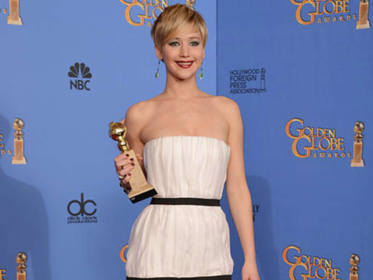 Jennifer Lawrence poses in the press room with the award for best supporting actress for