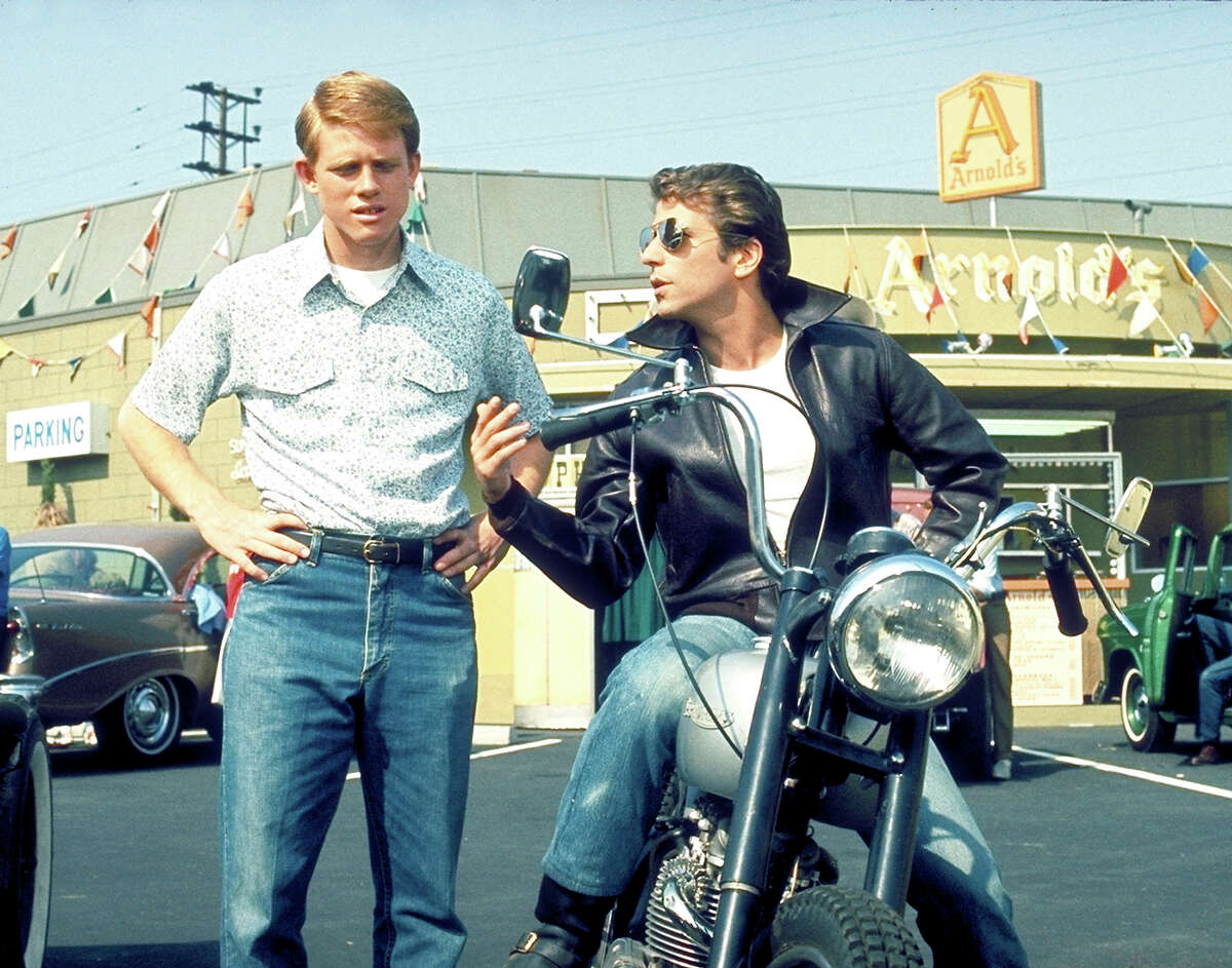 """Ron Howard as Richie Cunningham and Henry Winkler at Arthur Fonzarelli (on his beloved 1949 Triumph Trophy TR5) star in """"Happy Days,"""" which debuted in 1974. The show took viewers living in a turbulent Vietnam War-era time back to the 1950s. Let's take a look back at the cast."""