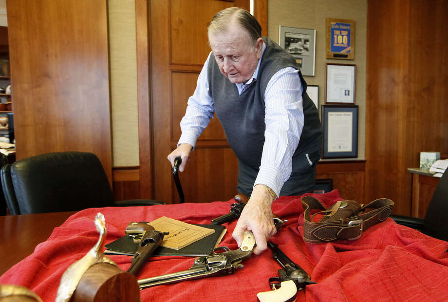 "B.J. ""Red"" McCombs reaches for a 1933 pistol during an interview in his San Antonio office. It's part of his extensive collection. / Prime Time Newspapers 2014"