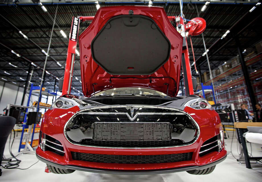 A view of a fully electric Tesla car on an assembly line at the new Tesla Motors car factory in Tilburg, the Netherlands, during the opening and launch of the new factory, on August 22, 2013. The American electric car manufacturer Tesla Motors, led by American-South African inventor and entrepreneur Elon Musk, will be assembling fully electric cars for the European market in this new factory. AFP PHOTO / ANP / GUUS SCHOONEWILLE   ***Netherlands out***        (Photo credit should read Guus Schoonewille/AFP/Getty Images) Photo: AFP, AFP/Getty Images / 2013 AFP