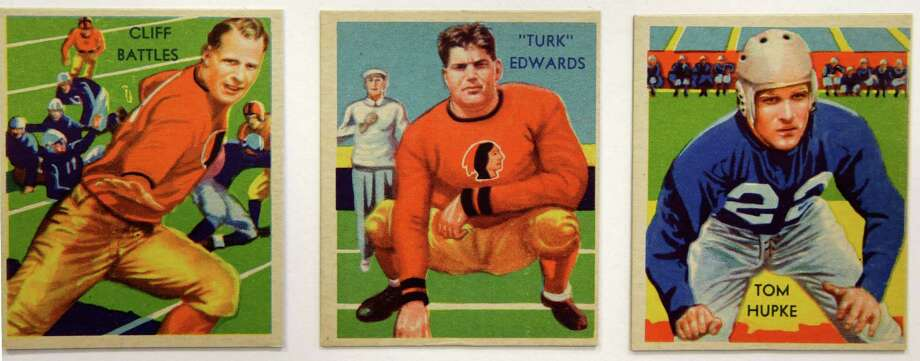 Cliff Battles, Turk Edwards, and Tom Hupke are among a set of 1935 National Chicle Gum Company vintage football trading cards, shown Wednesday, Jan. 8, 2014, at the Metropolitan Museum of Art. Edwards's nine-year NFL career with the Redskins ended after an injury during a coin toss. 150 football trading cards, including a series from 1894, are part of approximately 600 cards from the museum's vast collection of sport trade cards donated to the Met by the late hobby pioneer Jefferson Burdick. The exhibit runs Jan. 24 through Feb. 10. (AP Photo/Kathy Willens) ORG XMIT: NYKW105 Photo: Kathy Willens, AP / AP