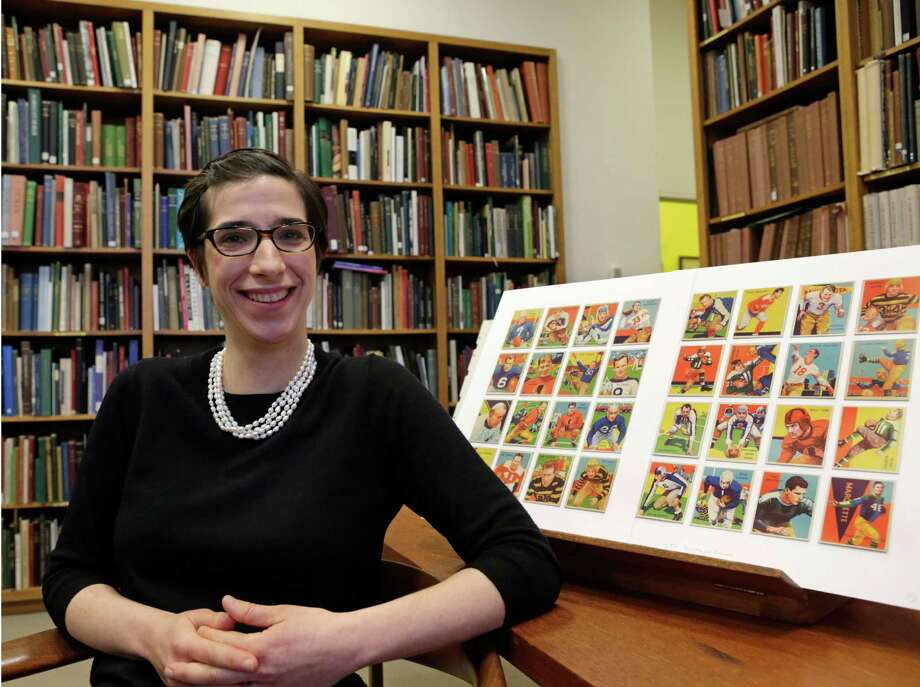 Assistant curator Freyda Spira, of the department of drawings and prints, poses with football cards, Wednesday, Jan. 8, 2014, part of an exhibition to be mounted at the Metropolitan Museum of Art in New York. The museum better known for high art, is presenting a pop-up exhibition celebrating football's history through the ages with vintage trading cards. The 150 cards, including a series from 1894, are part of approximately 600 football cards from the museum's vast collection of sport trade cards donated to the Met by the late hobby pioneer Jefferson Burdick. The exhibit opens Jan. 24 and runs through Feb. 10. (AP Photo/Kathy Willens) ORG XMIT: NYKW101 Photo: Kathy Willens, AP / AP