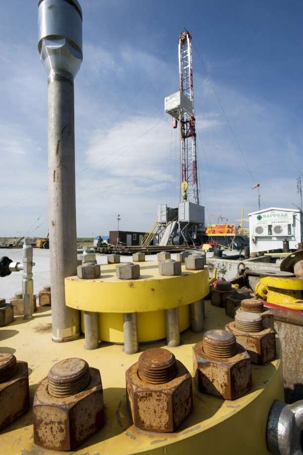 A derrick mast stands behind a spare capped well head at San Leon Energy Plc's Chopin-1 shale gas exploration well in Pinczow, Poland, on Sunday, Sept. 18, 2011. Photo: John Guillemin, Bloomberg
