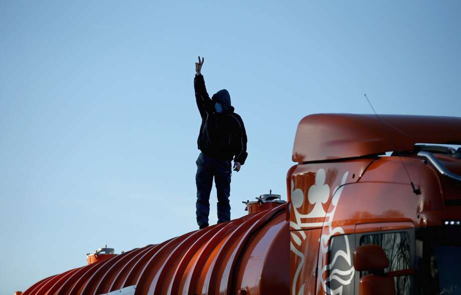 An anti-fracking protester stands on the top of a truck carrying chemicals to the Barton Moss gas fracking facility on January 13, 2014 in Barton, England. Environmental protesters and anti-gas fracking campaigners blocked roads and climbed on trucks arriving at the Barton Moss gas exploration site. Photo: Christopher Furlong, Getty Images