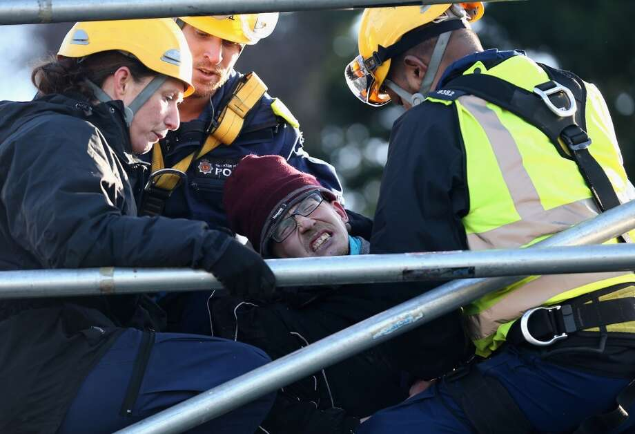 Police officers restrain an anti-fracking protester standing on the top of a truck carrying chemicals to the Barton Moss gas fracking facility on January 13, 2014 in Barton, England. Environmental protesters and anti gas fracking campaigners blocked roads and climbed on trucks arriving at the Barton Moss gas exploration site. Photo: Christopher Furlong, Getty Images