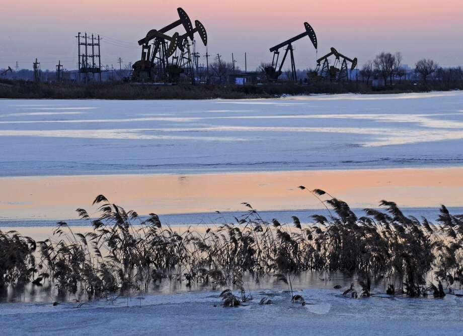 Oil rigs belonging to PetroChina are seen near the banks of a snow covered lake in Daqing in northeastern China's Heilongjiang province in March 2012. Photo: Anonymous, Associated Press