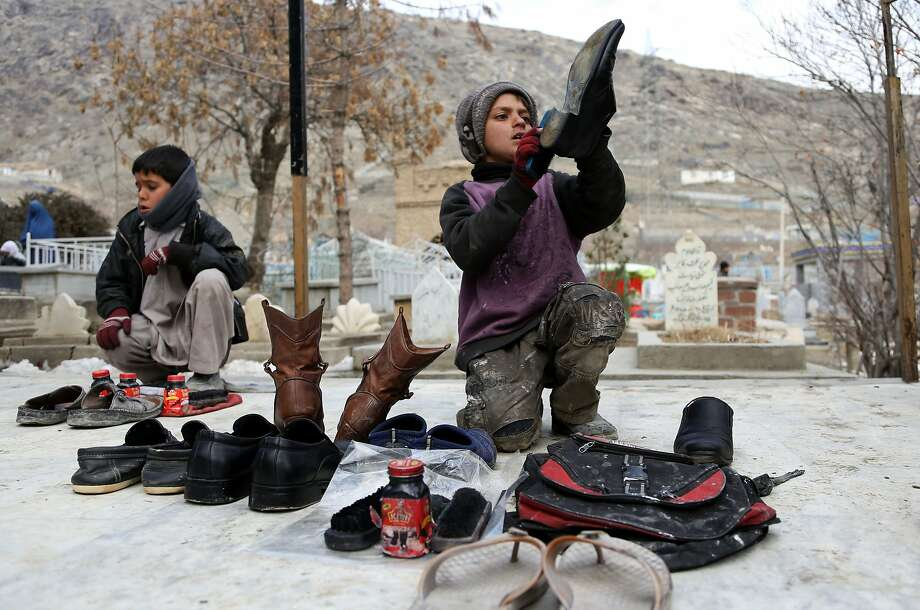 Buffing leather in cold weather:Afghan boys polish shoes in the snow in Kabul for a couple of dollars a day. Photo: Rahmat Gul, Associated Press