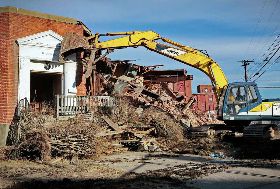 In this Monday, Jan. 13, 2014 photo, an excavator operator demolishes the entrance to the former headquarters of the Berkshire Hathaway mill, where investor Warren Buffett first made his mark, in New Bedford, Mass. Buffett, then an ambitious 34-year-old investor, acquired control of the textile manufacturer in 1965. Overwhelmed by foreign competition, he closed it in 1985 and later sold the 18-acre complex for $215,000. (AP Photo/The Standard-Times, Peter Pereira) ORG XMIT: MABED101 Photo: Peter Pereira / The Standard-Times