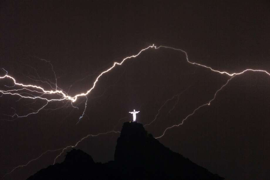 Lightning flashes over a glowing Christ the Redeemer statue on top of Corcovado Hill in Rio de Janeiro. Photo: Yasuyoshi Chiba, AFP/Getty Images