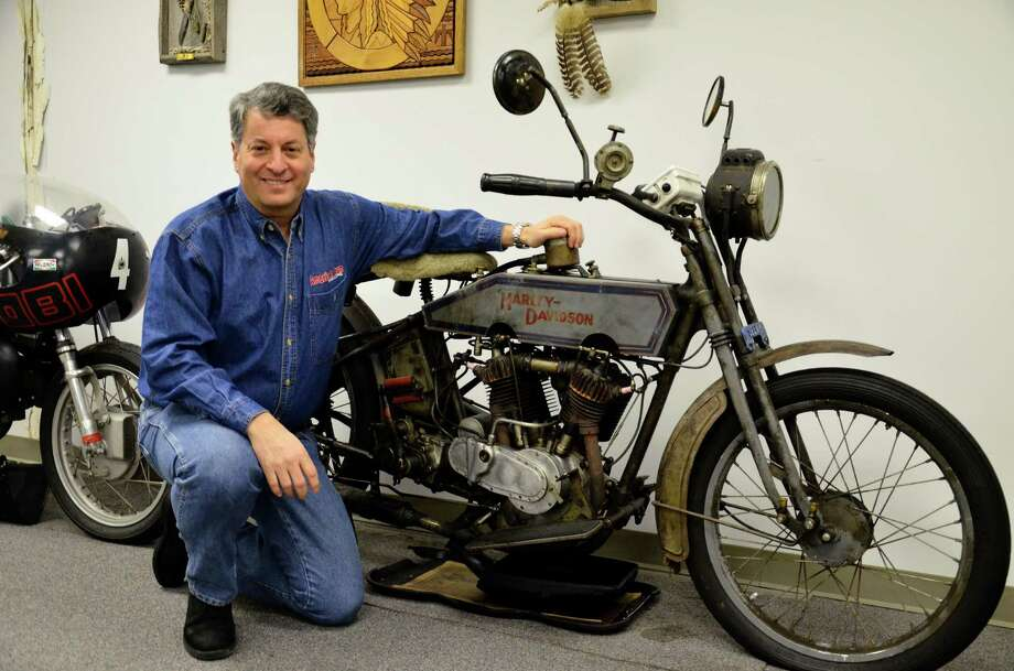 Buzz Kanter and one of his vintage motorcycles at the TAM Communications office in Stamford, Conn. Kanter, a New Canaan Board of Finance alternate member whose real first name is John, rode this 1915 Harley Davidson from North Carolina to Los Angeles during the first Motorcycle Cannonball Run in 2010. Photo: Nelson Oliveira / New Canaan News