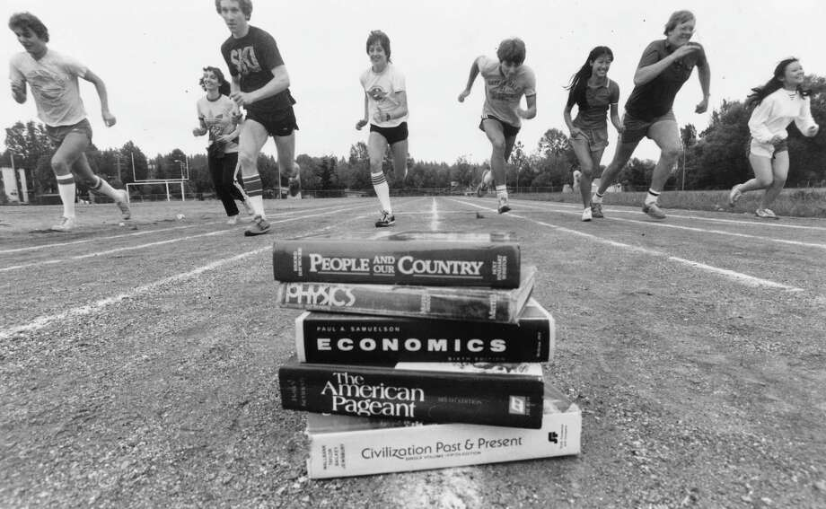 Why are these kids running toward a pile of books? No explanation. This June 6, 1983, photo shows (left to right) Geoff Dillard, Wendy Spizman, Dave Steele, Sarah Bolender, David Ovens, Millie Yen, Pieter van Zee and Kathy Hsieh, who were seniors with high GPAs that year. Photo: copyright MOHAI, Seattle Post-Intelligencer collection, 2000.107_print_schools_hale_015. Photo: Copyright MOHAI