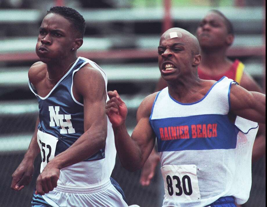 Intense running in the '90s: Johnnie Williams, left, of Nathan Hale runs against Antonio Conley of Rainier Beach, right, in a championship 100-meter dash on May 17, 1996.  Photo: LOREN CALLAHAN, Copyright MOHAI