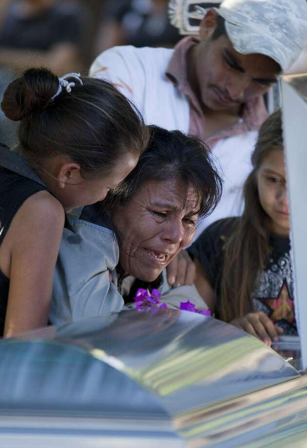 Juana Perez cries for her son Rodrigo Benitez, 25, killed in cross fire between military troops and vigilantes in Antunez. Photo: Eduardo Verdugo, Associated Press