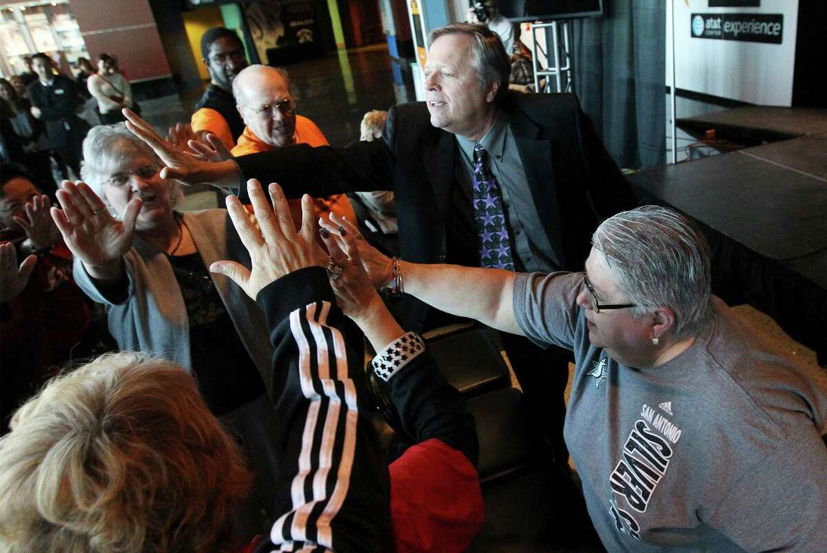 San Antonio Stars basketball head coach Dan Hughes gathers fans for a collective high-five during a presser to announce the team's name change - formerly the Silver Stars - and to show off their new logo at the AT&T Center on Tuesday, Jan. 14, 2014. The Stars also announced their first ever marquee sponsor, H-E-B.