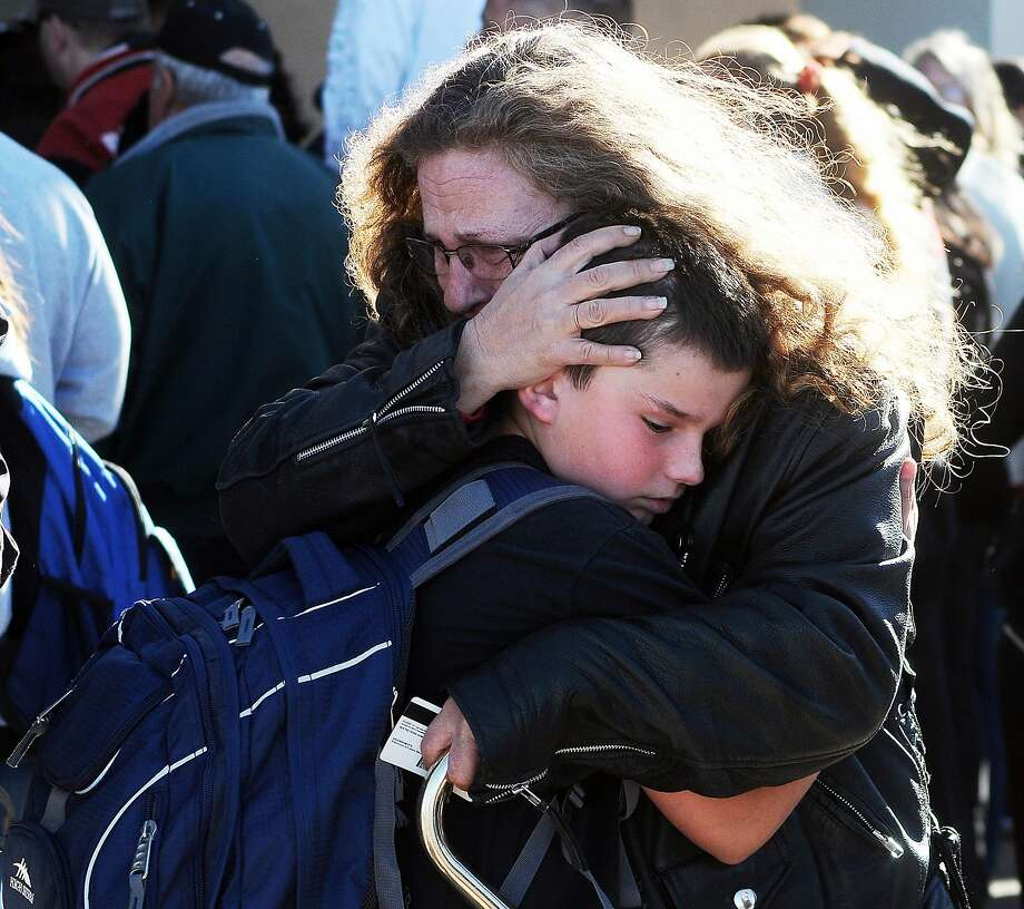A woman hugs a student at a staging ground set up at Roswell Mall after a middle school shooting. Photo: Mark Wilson, Associated Press