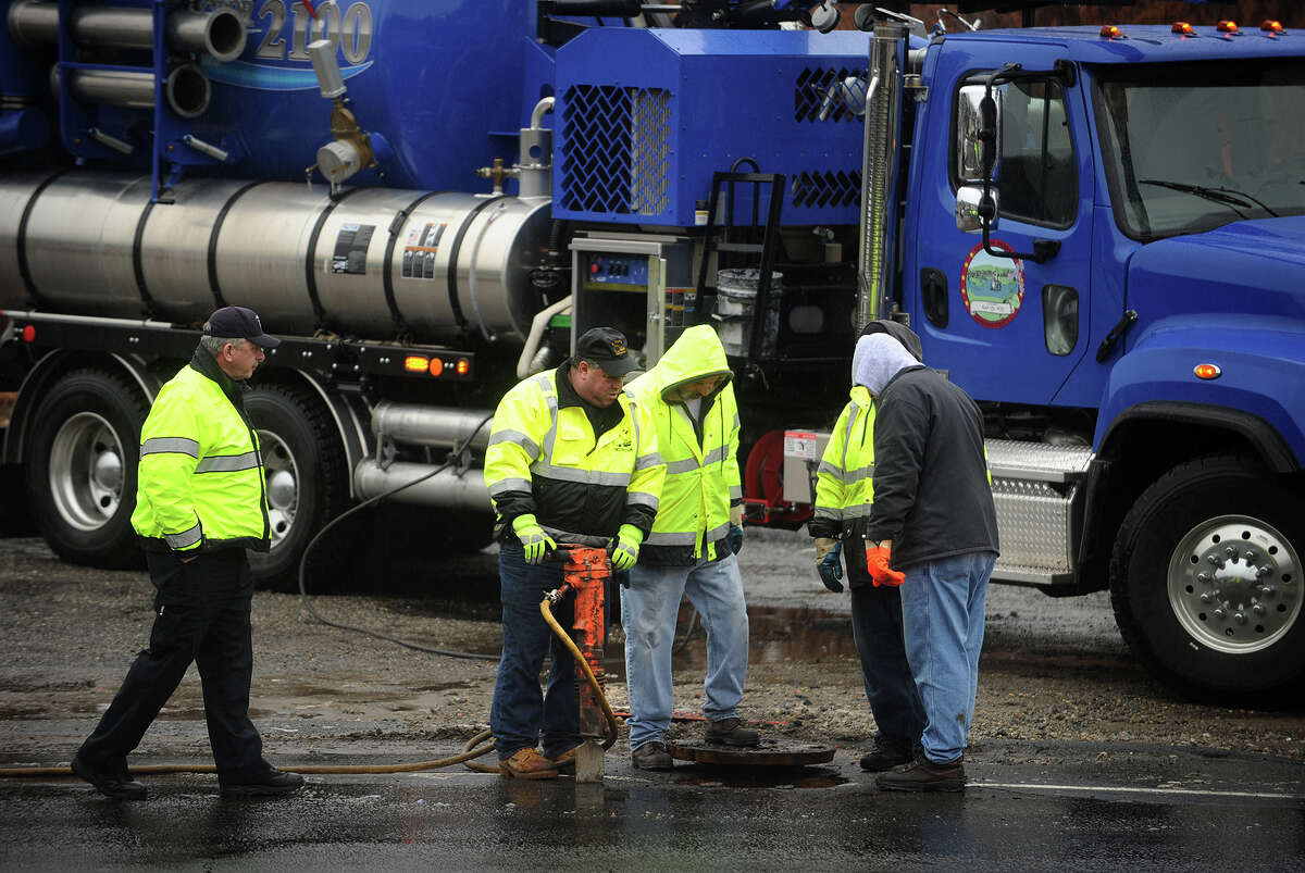Workers open a manhole cover on New Haven Avenue in Derby, Conn. after a blocked sewer pipe released raw sewage on to the road on Tuesday morning, January 14, 2014. John Saccu, chairman of the Water Pollution Control Authority, said that Department of Energy and Environmental Protection officials will determine the estimated flow and whether any of the sewage reached the nearby Housatonic River.