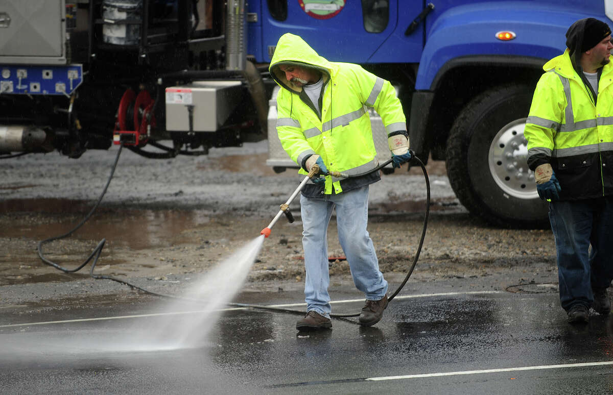A worker hoses spilled sewage from New Haven Avenue in Derby, Conn. after a blocked sewer pipe overflowed on Tuesday morning, January 14, 2014. John Saccu, chairman of the Water Pollution Control Authority, said that Department of Energy and Environmental Protection officials will determine the estimated flow and whether any of the sewage reached the nearby Housatonic River.