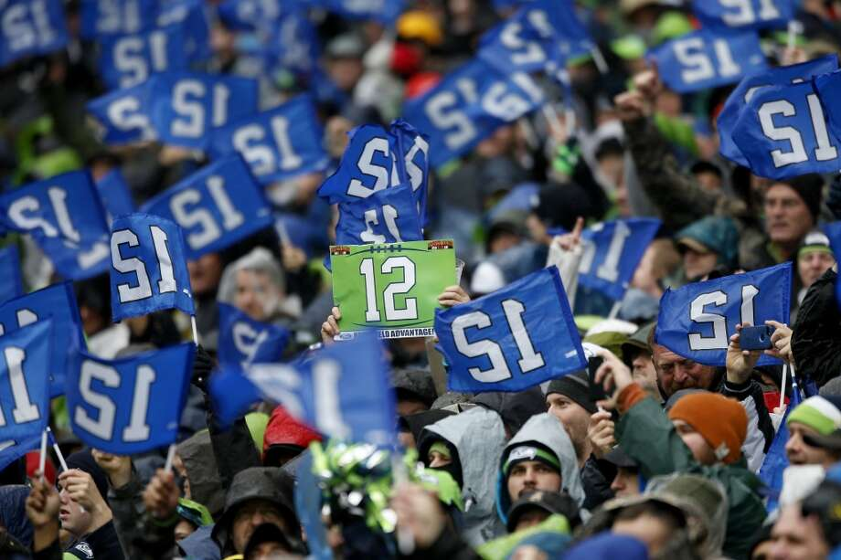Seattle Seahawks fans hold up 12th Man signs as the Seahawks take on the New Orleans Saints on January 11, 2014. Photo: Otto Greule Jr, Getty Images