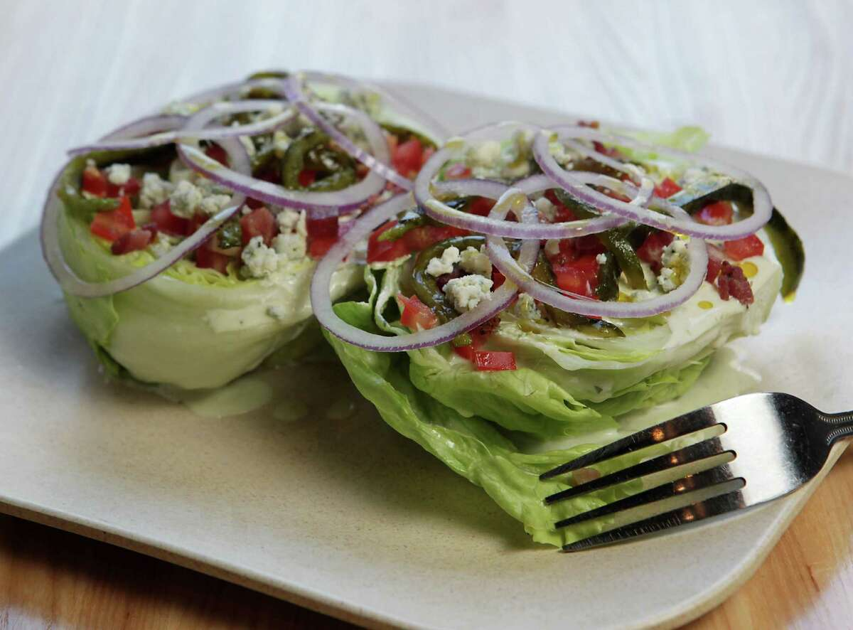 Wedge salad consists of iceberg lettuce, smoked bacon lardons, tomatoes, shaved red onions, grilled poblano and blue cheese ranch at Fielding's Wood Grill.