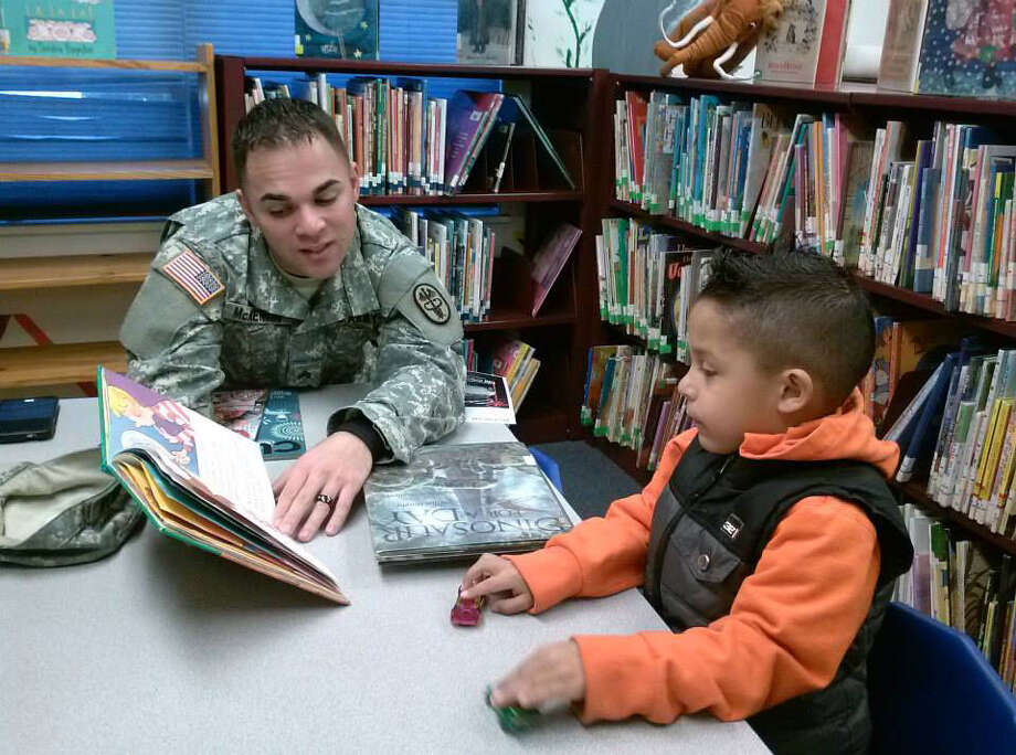 U.S. Army Sgt. Jason McKennon reads to his son, Xaidyn, 5, during a recent visit to the Universal City Public Library. Photo: Courtesy Photo