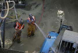 Construction workers spray water on equipment at the entrance to the Central Subway project at Fourth and Bryant streets in San Francisco, Calif. on Tuesday, Jan. 14, 2014. With three major transportation projects wrapping up last year, the tunneling project for Muni's new subway line is among the few still underway.