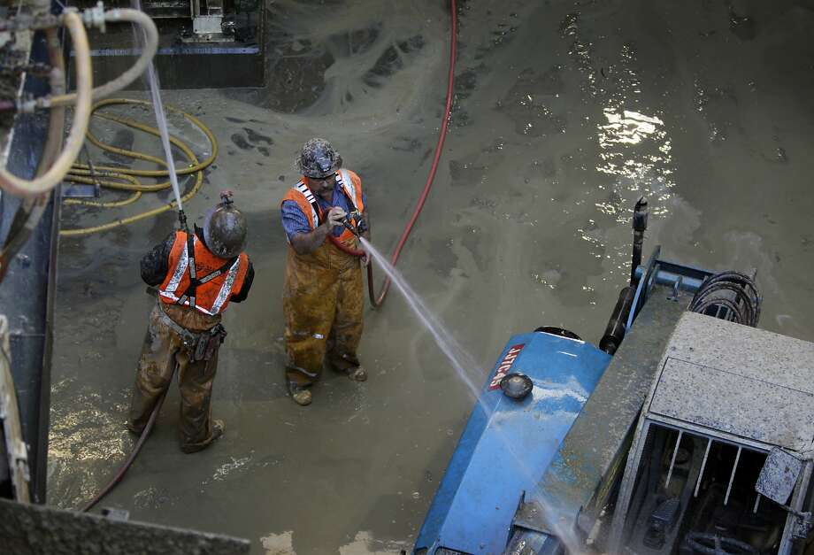 Construction workers spray water on equipment at the entrance to the Central Subway in San Francisco, just one of many big infrastructure projects in the works. Photo: Paul Chinn, The Chronicle