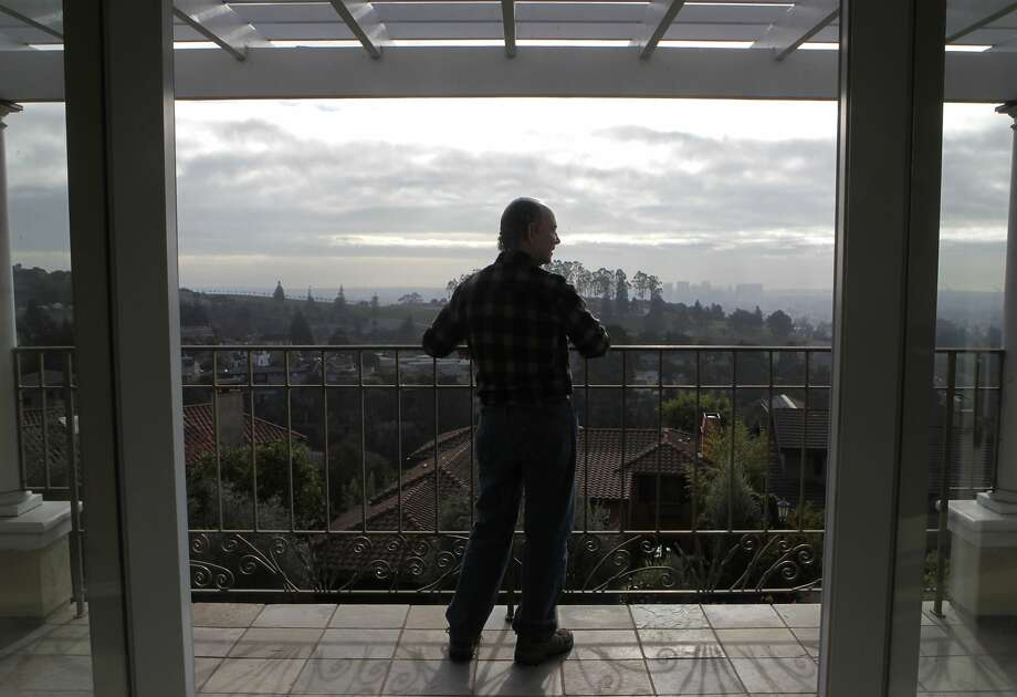 Jeff Kahn takes in the hazy view from the deck of his home in the Oakland hills. He says  he has used his fireplace just three times this winter partly because of Spare the Air days. Photo: Paul Chinn, The Chronicle
