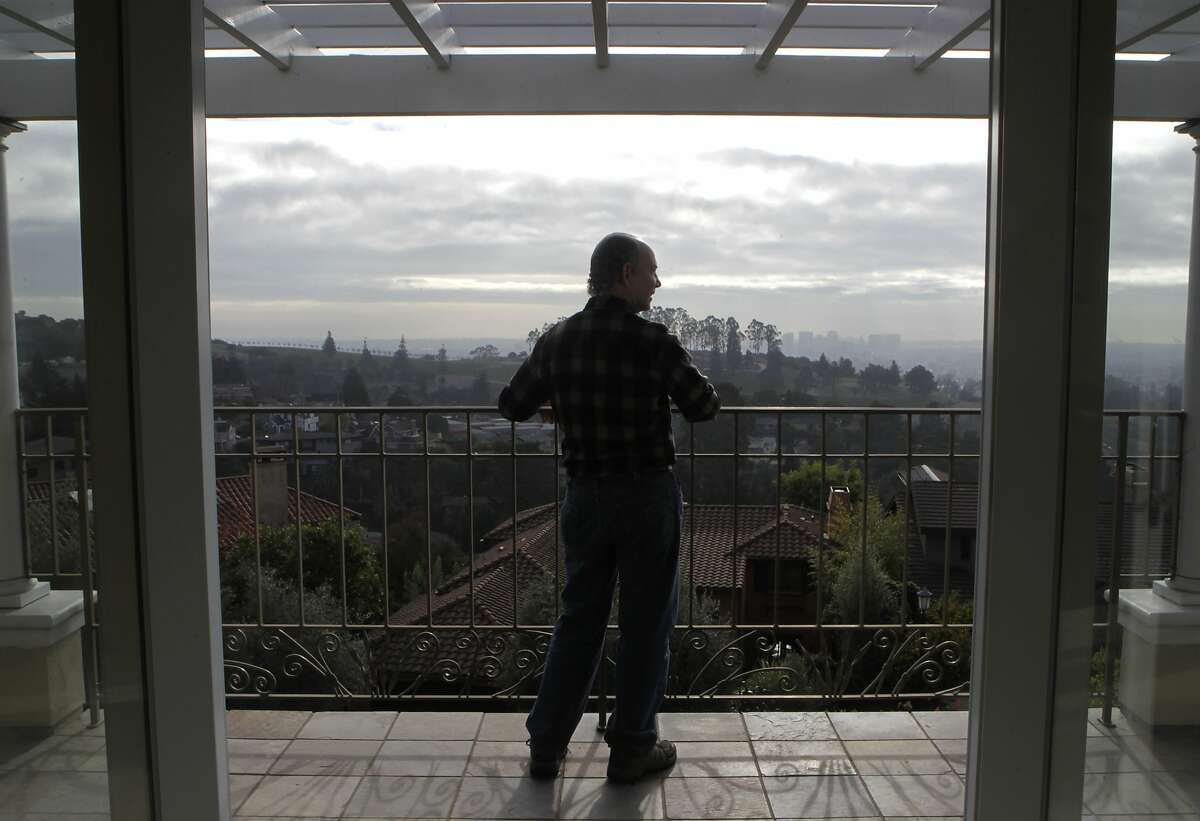 Jeff Kahn takes in the hazy view from the deck of his home in Oakland, Calif. on Tuesday, Jan. 7, 2014. Unseasonably warm and dry weather has resulted in unusual hazy conditions and a high number of Spare the Air days.