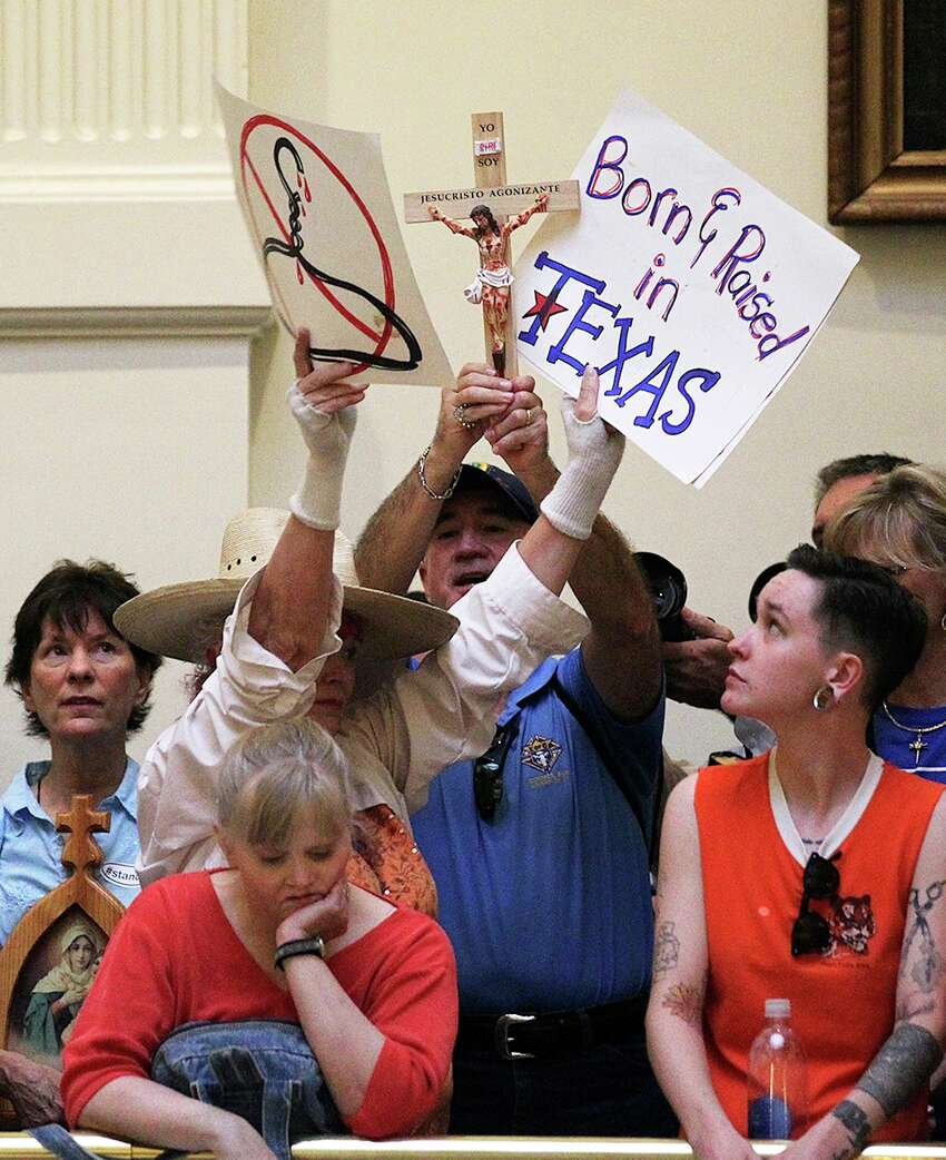 Abortion bill protesters, in orange, and those for the bill in blue, gather at the State Capitol for the start of the second special session, Monday, July 1, 2013.