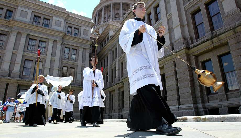 Altar boys from St. Mary's Cathedral in Austin lead a march around the Capitol building as the House of Representatives debates amendments to abortion legislation on July 9, 2013. Photo: TOM REEL, San Antonio Express-News / San Antonio Express-News