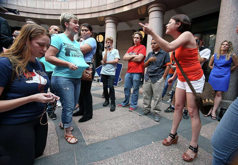 Jessica Davis (left) kneels to pray with her rosary as Julie Ann Nitsch (right) and Pamela Whitehead argue as supporters of both sides of the issue fill the Capitol building in Austin as a special committee hears testimony on Senate Bill 2  on July 1, 2013. Photo: TOM REEL, San Antonio Express-News / San Antonio Express-News