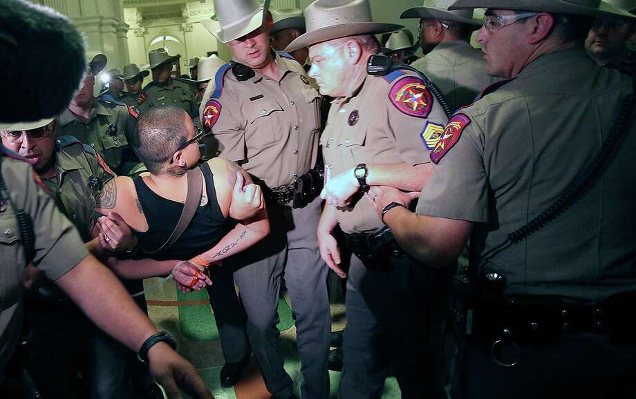 A protester is hauled away by DPS officers after the Senate passes abortion legislation on July 12, 2013. Photo: TOM REEL
